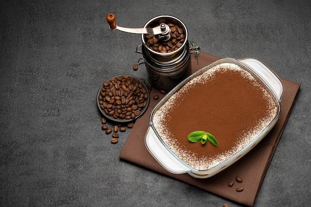 Tradycyjny włoski deser tiramisu w szklanym naczyniu do pieczenia i młynku do kawy na betonowym tle lub stole