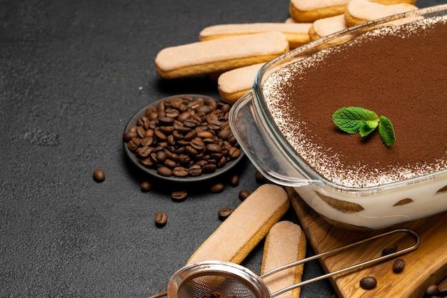 Tradycyjny włoski deser tiramisu w szklanym naczyniu do pieczenia na drewnianej desce do krojenia i ciasteczka savoiardi na betonowym tle lub stole