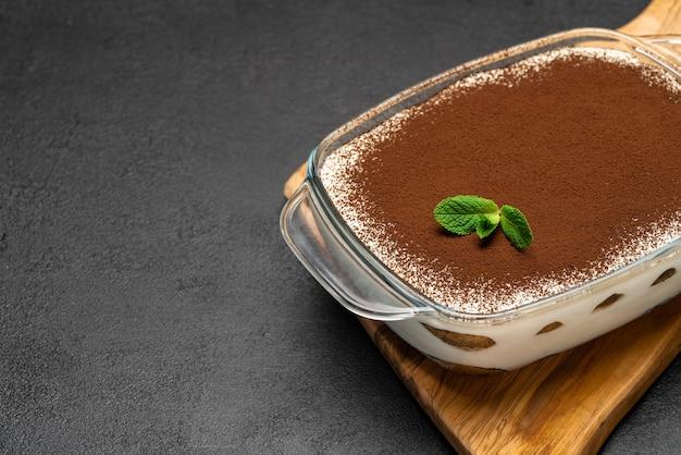 Tradycyjny włoski deser tiramisu w szklanym naczyniu do pieczenia na drewnianej desce do krojenia na betonowym tle lub stole