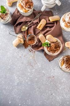 Tradycyjny włoski deser tiramisu. wiele szklanek z domowym tiramisu z czekoladowym proszkiem kakaowym, szarym kamieniem lub betonowym tłem.