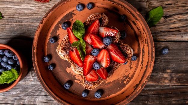 Tradycyjny włoski deser tiramisu z truskawkami i jagodami