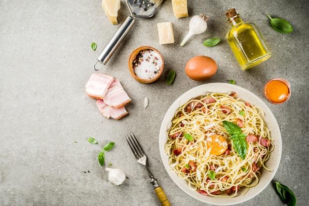 Tradycyjny włoski makaron, spaghetti carbonara z boczkiem, kremowy sos, parmezan, żółtko i świeża bazylia