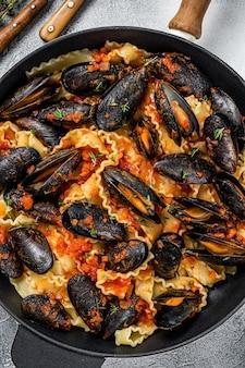 Tradycyjny włoski makaron z owocami morza z małżami, spaghetti i sosem pomidorowym. białe tło. widok z góry.