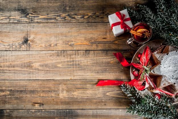Tradycyjny włoski świąteczny tort owocowy panettone pandoro z świąteczną czerwoną wstążką i pudełkiem na ozdoby świąteczne i grzane wino