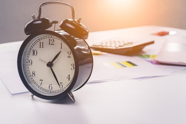 Tradycyjny zegar i arkusz kalkulacyjny na biurku z laptopem