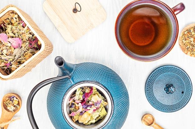 Tradycyjny zestaw do ceremonii parzenia herbaty, imbryk i filiżanka z ziołami i suszoną herbatą owocową. tisane detox, relaks, uzdrawianie, zdrowe pocieszenie, koncepcja herbaty. widok z góry, płaski układ