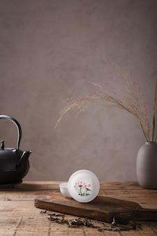 Tradycyjny zestaw do herbaty azjatyckiej - czajnik z czarnego żelaza i ceramiczne filiżanki do ceremonii parzenia herbaty na drewnianym stole. zabytkowy styl. z miejscem na tekst. chiny, herbata, zastawa stołowa, tradycja, zdrowie, ceremonia parzenia herbaty, azja.