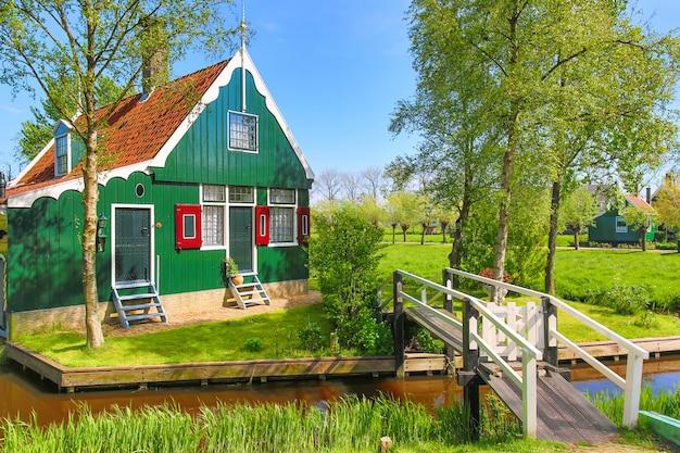 Tradycyjny zielony holendera dom z małym drewnianym mostem przeciw niebieskiemu niebu w zaanse schans wiosce, holandie