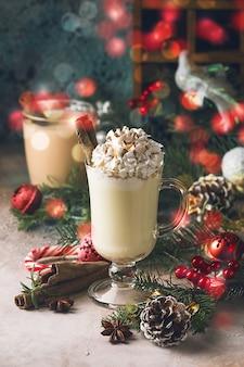 Tradycyjny zimowy ajerkoniak w szklanym kubku z mlecznym rumem i cynamonem, ozdobiony dekoracjami świątecznymi z bitej śmietany