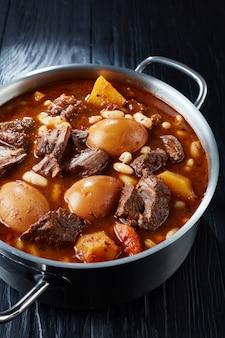Tradycyjny żydowski cholent hamin - danie główne na posiłek szabatowy wolno gotowana wołowina z ziemniakami, fasolą i brązowymi jajkami w garnku na czarnym drewnianym stole, widok pionowy z góry, zbliżenie