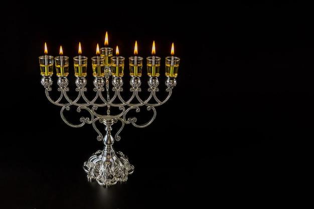 Tradycyjny żydowski symbol święta chanuka judaizmu z menorą z palącymi się świecami oliwnymi
