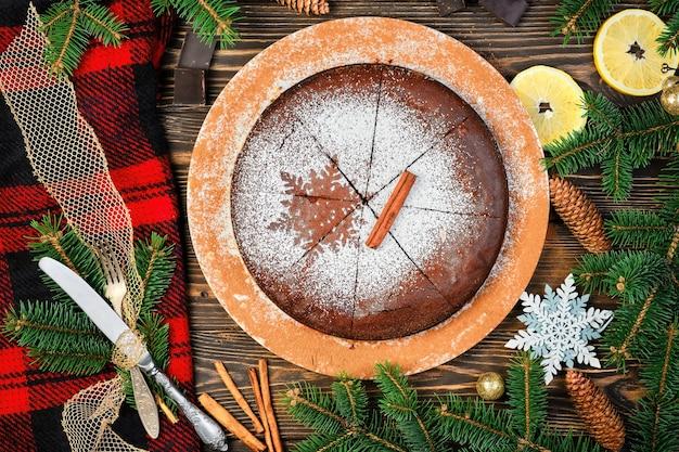 Tradycyjnym domowym deserem jest ciasto czekoladowe. świąteczne ciasto na ciemnym drewnianym stole ozdobionym gałęziami choinki. widok z góry na lepki szwedzki placek kladdkaka