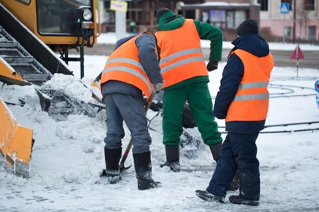 Traktor odśnieżający drogę. koparka oczyszcza ulice z dużych ilości śniegu w mieście. pracownicy zamiatają śnieg z drogi w zimie, czyszczenie drogi przed burzą śnieżną.