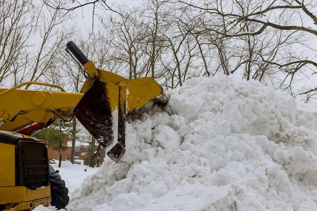 Traktor odśnieżający oczyszcza drogę po obfitych opadach śniegu.