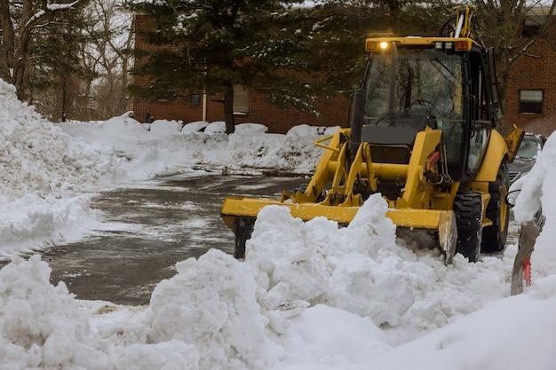 Traktor odśnieżający toruje drogę po obfitych opadach śniegu.