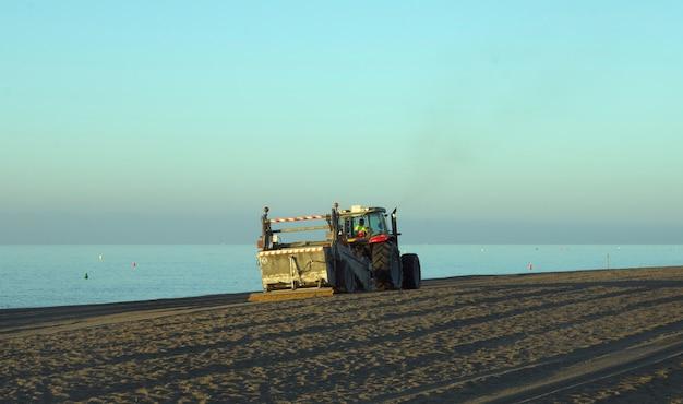 Traktor przesuwający piasek po plaży