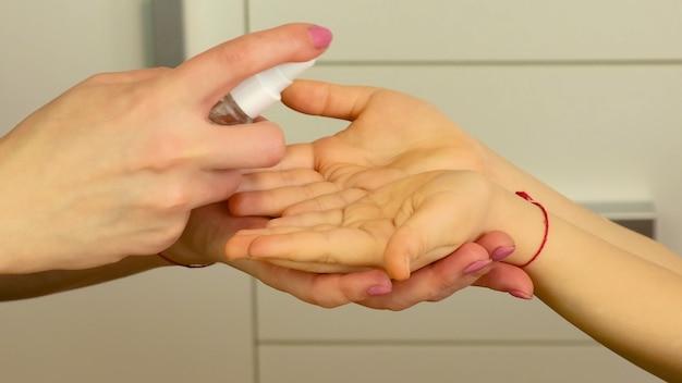 Traktuj ręce dziecka środkami antyseptycznymi. selektywna ostrość. ludzie