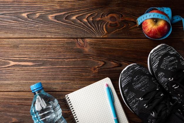 Trampki fitness, butelka wody, czerwone jabłko z taśmą i notatnik na drewnianym
