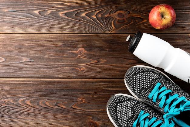 Trampki fitness, butelka wody i jabłko