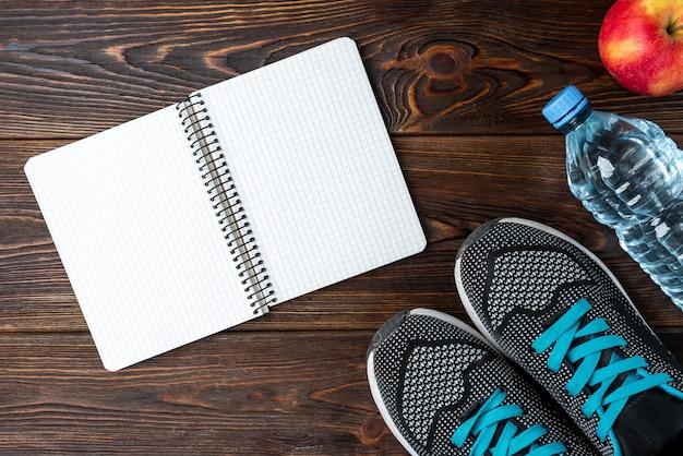 Trampki fitness, butelka wody i notatnik na ciemnym drewnianym