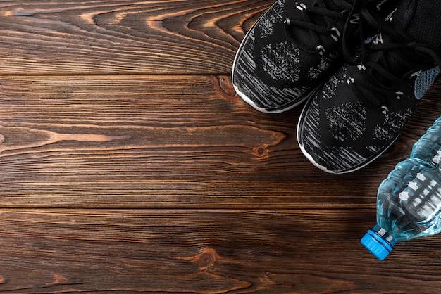 Trampki fitness i butelka wody na drewnianym