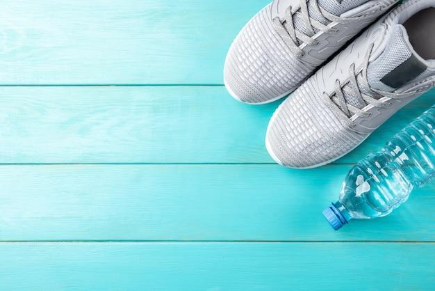 Trampki fitness i butelka wody na niebieskim tle drewnianych.