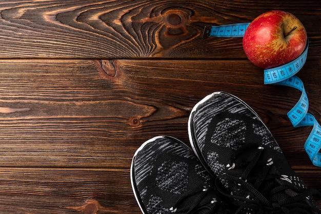 Trampki fitness i czerwone jabłko z taśmą na drewnianym