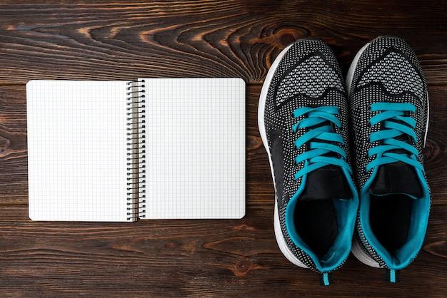 Trampki fitness i notatnik na ciemnym drewnianym