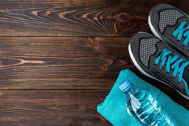 Trampki fitness i ręcznik na ciemnym drewnianym