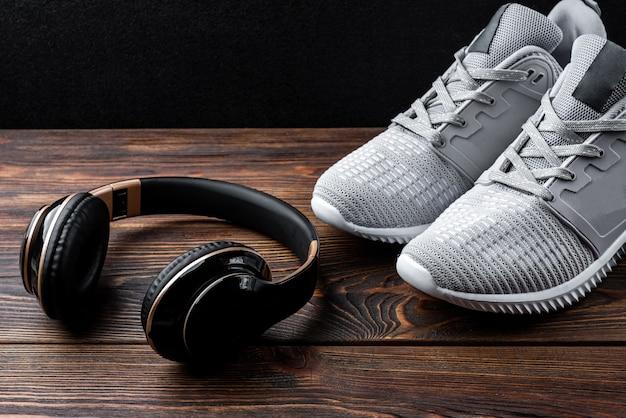 Trampki fitness i słuchawki na ciemnym tle drewnianych.