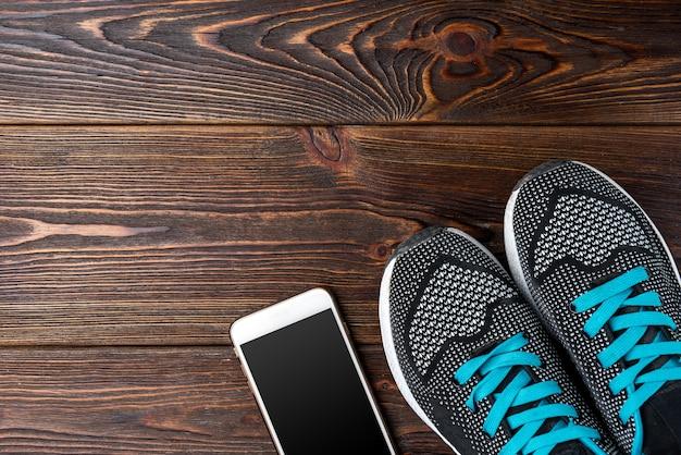 Trampki fitness i telefon komórkowy na ciemnym drewnianym