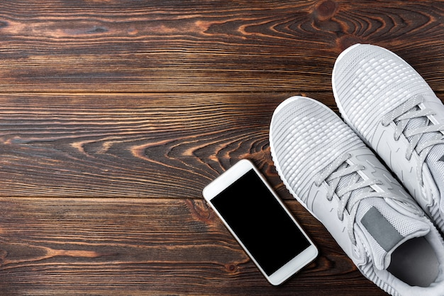 Trampki fitness i telefon komórkowy na ciemnym tle drewnianych.