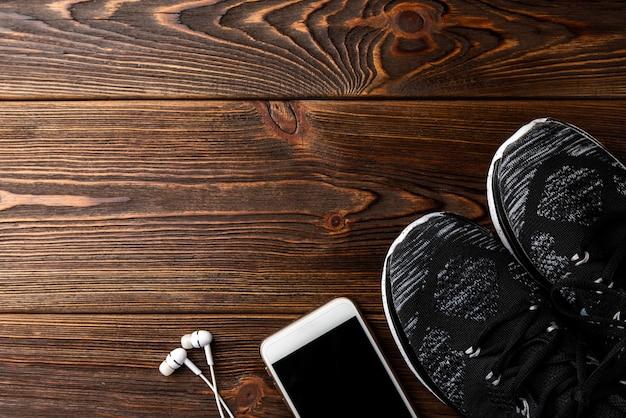 Trampki fitness i telefon komórkowy ze słuchawkami na drewnianym