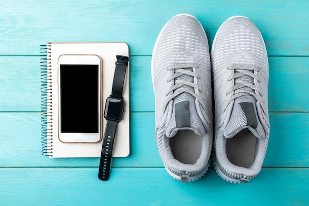 Trampki fitness, notatnik, telefon komórkowy i bransoletka fitness na niebieskim tle drewnianych.