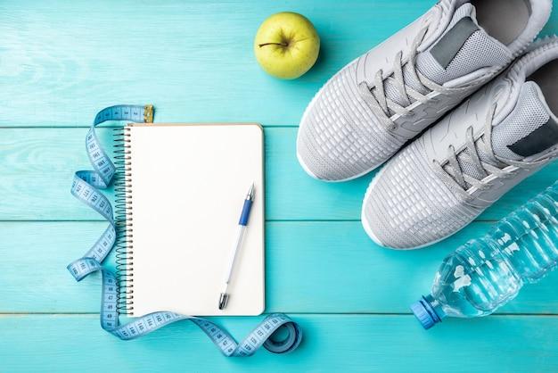 Trampki fitness, notatnik, zielone jabłko, taśma miernicza i butelka wody na niebieskim tle drewnianych