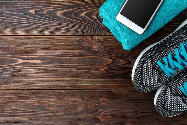 Trampki fitness, ręcznik i telefon komórkowy na ciemnym drewnianym