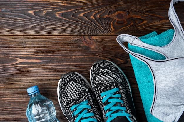 Trampki fitness, ręcznik i woda na ciemnym drewnianym