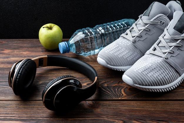 Trampki fitness, słuchawki, jabłko i butelka wody na ciemnym tle drewnianych.