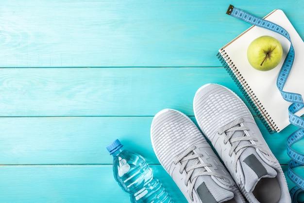 Trampki fitness, zielone jabłko, taśma miernicza i butelka wody na niebieskim tle drewnianych.