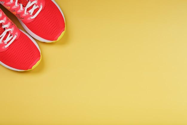 Trampki sportowe, różowe na żółtym tle z wolną przestrzenią. widok z góry, minimalistyczna koncepcja