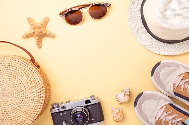 Trampki, torba rattanowa, okulary przeciwsłoneczne, kapelusz i aparat retro na żółtym tle. koncepcja podróży. leżał płasko