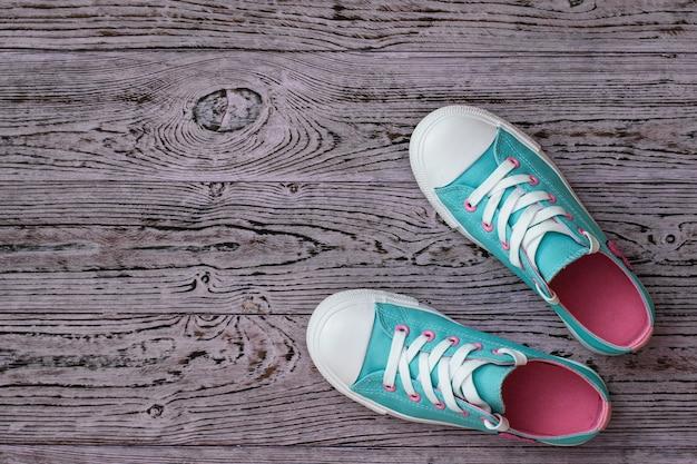 Trampki wykonane z turkusowo-różowej tkaniny na drewnianej podłodze. styl sportowy. leżał na płasko. widok z góry.