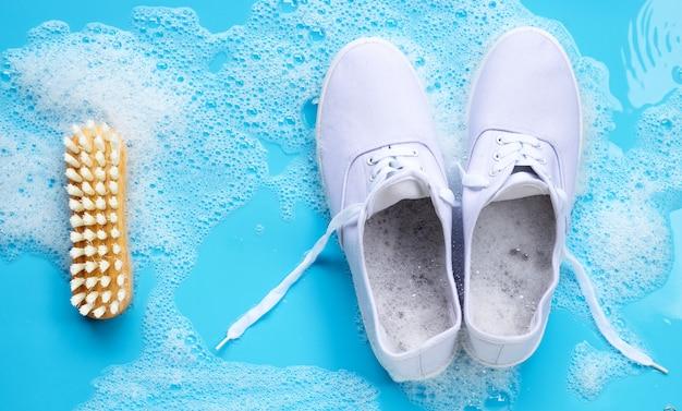 Trampki z pianką rozpuszczania detergentu w wodzie i drewnianą szczotką na niebieskim tle. prać brudne buty.