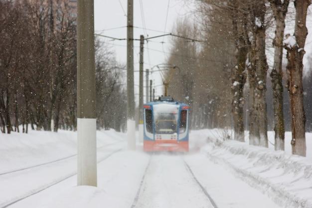 Tramwaj przejeżdżający wzdłuż linii podczas burzy śnieżnej