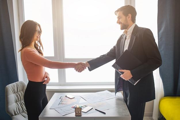 Transakcja biznesowa między młodym mężczyzną i kobietą drżenie rąk