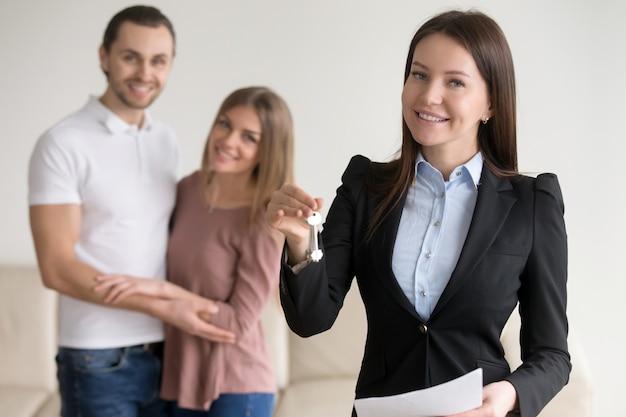 Transakcja dotycząca nieruchomości. żeński uśmiechnięty pośrednik handlu nieruchomościami pokazuje klucze mieszkanie