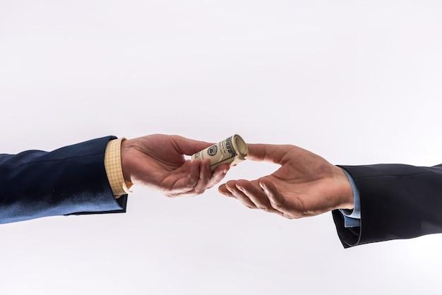 Transfer pieniędzy między dwoma biznesmenami. ręka mężczyzny dając 100 dolarów na szarym tle. finanse