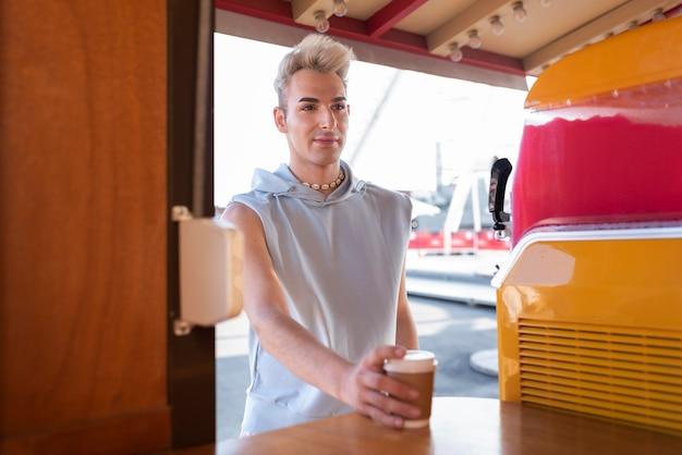 Transgender średniego strzału trzymający filiżankę kawy