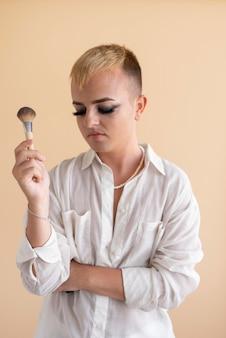 Transgender średniego strzału trzymający pędzel do makijażu