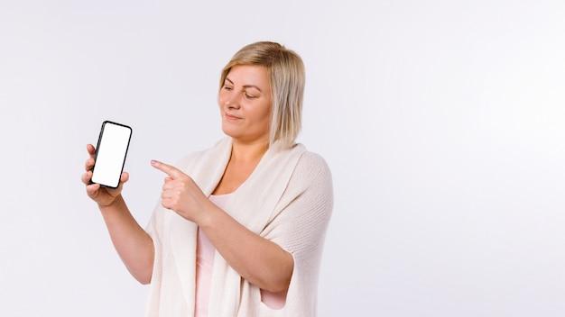 Transparent. kobieta ze smartfonem w dłoniach pokazuje ekran palcem wskazującym. białe tło i puste miejsce z boku. wysokiej jakości zdjęcie